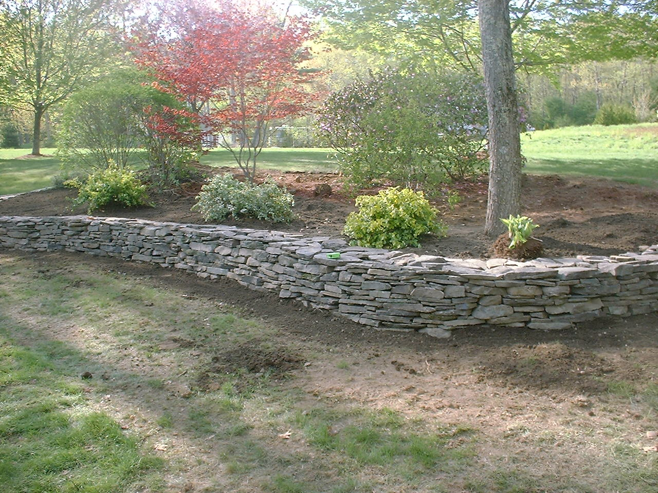 Landscape ideas on pinterest gas fire pits rock for Rock wall garden designs